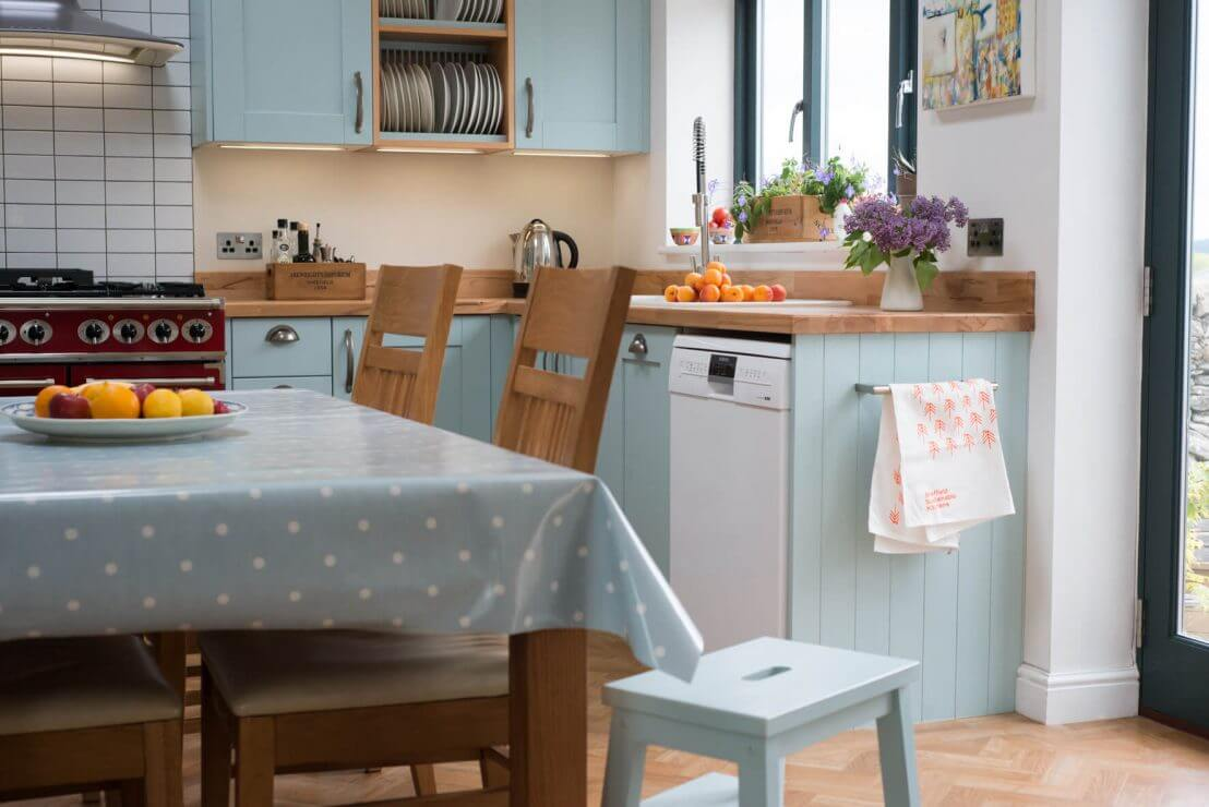 pale blue kitchen with dining table in centre