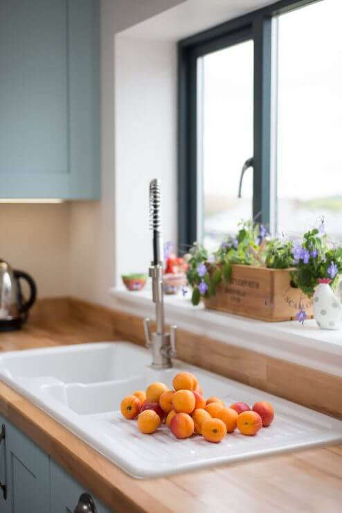 white ceramic sink in new kitchen with oranges on the draining board