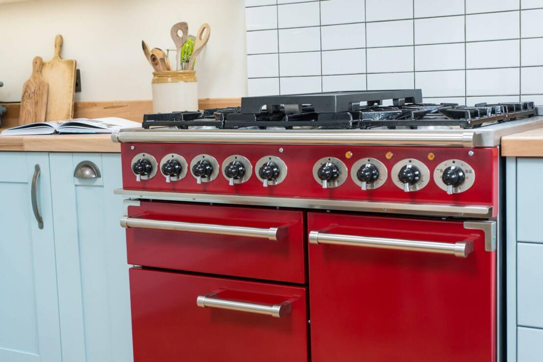 red range cooker with silver handles in blue kitchen