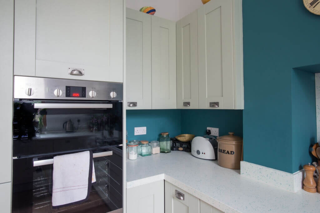 pale green L-shaped shaker kitchen
