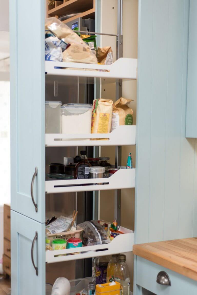 tall open kitchen cabinet larder unit containing food and kitchen supplies