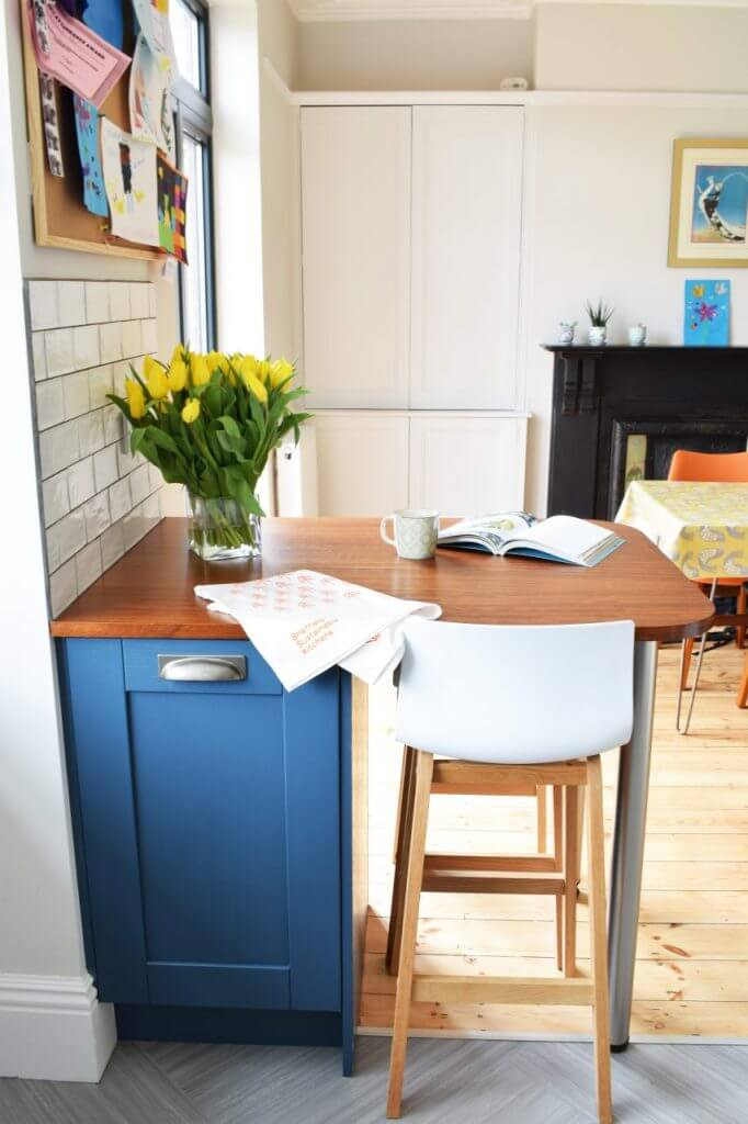 small breakfast bar made from reclaimed iroko timber with chair and blue kitchen cabinet