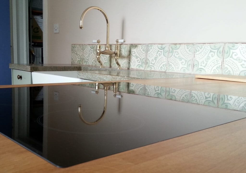 flush induction hob with kitchen tap reflection