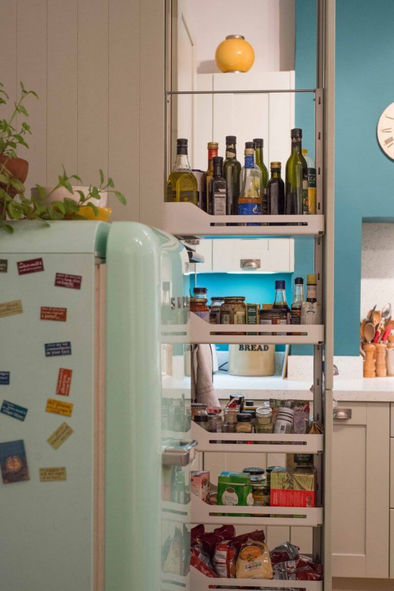 full height kitchen larder storage unit open to show jars tins and food supplies