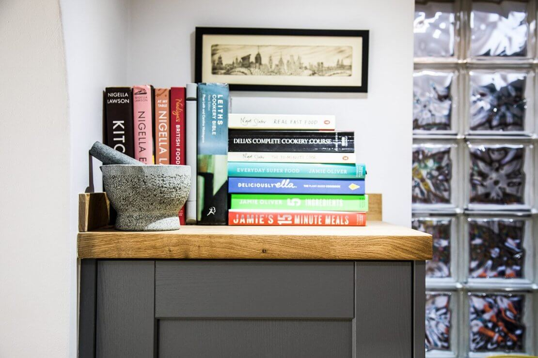top of kitchen cupboard with cookery recipe books and mortar and pestle