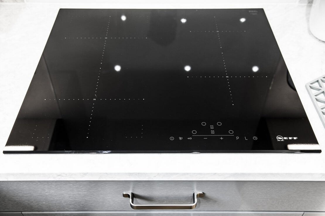 close up of neff induction hob and cutlery drawer with painted grey front