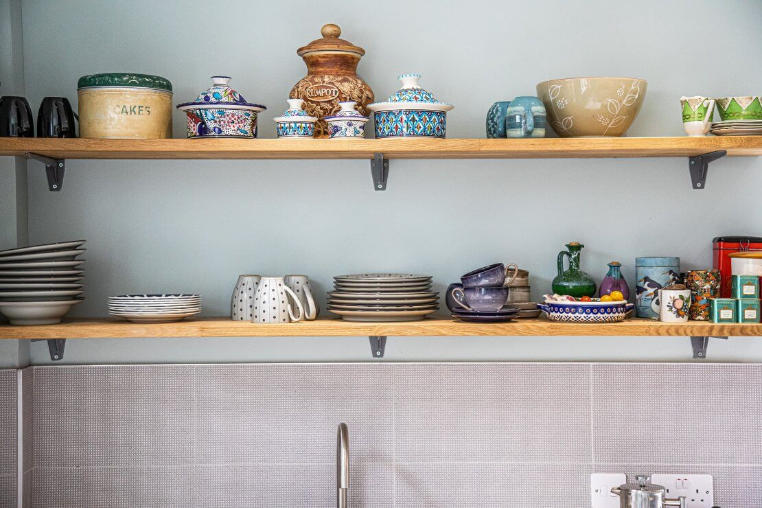 open timber shelves displaying crockery in sustainable kitchen
