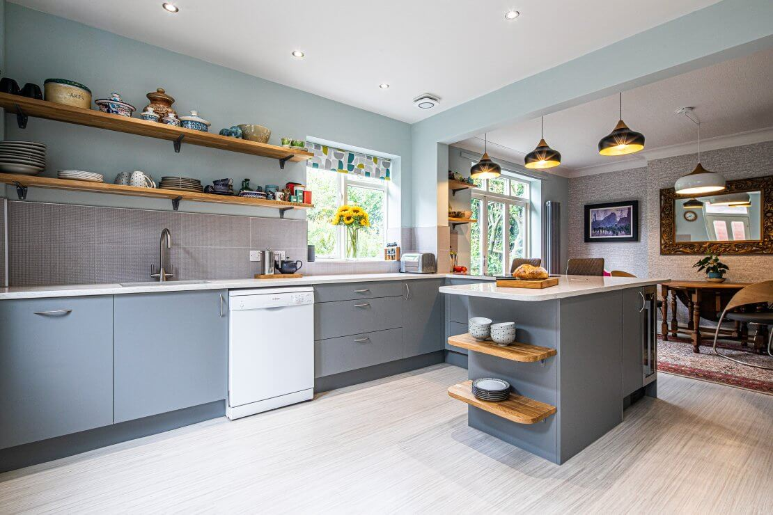 grey U-shaped kitchen with wooden shelving