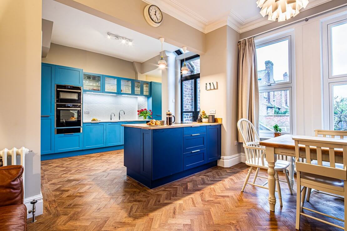kitchen in two toned blue with island and parquet floors