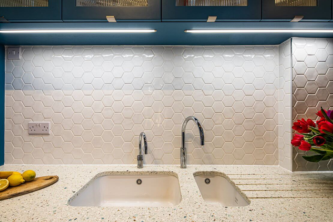 recycled glass kitchen worktop sink area with hexagon tiles and quooker tap