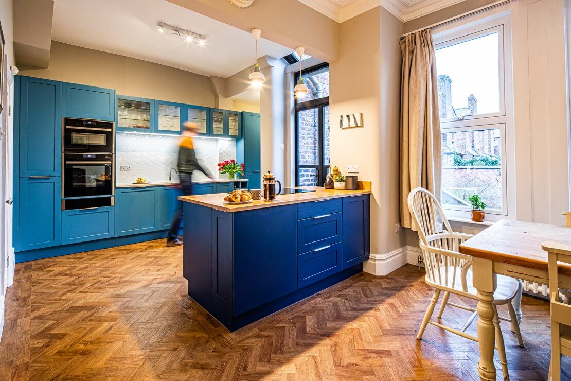 blue toned kitchen with parquet flooring