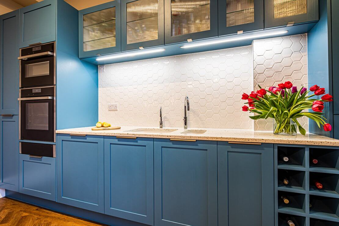 blue shaker kitchen cabinets with recycled glass worktop