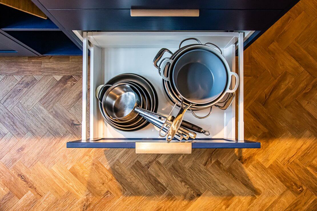 kitchen pans in drawer with blue shaker doors