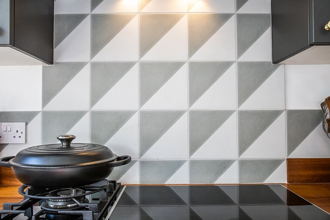 cooking pot on hob with tiled splashback in geometric grey and white triangles