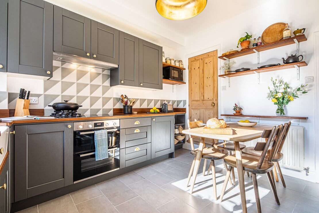 tiled kitchen wall with grey cabinets and timber dining table