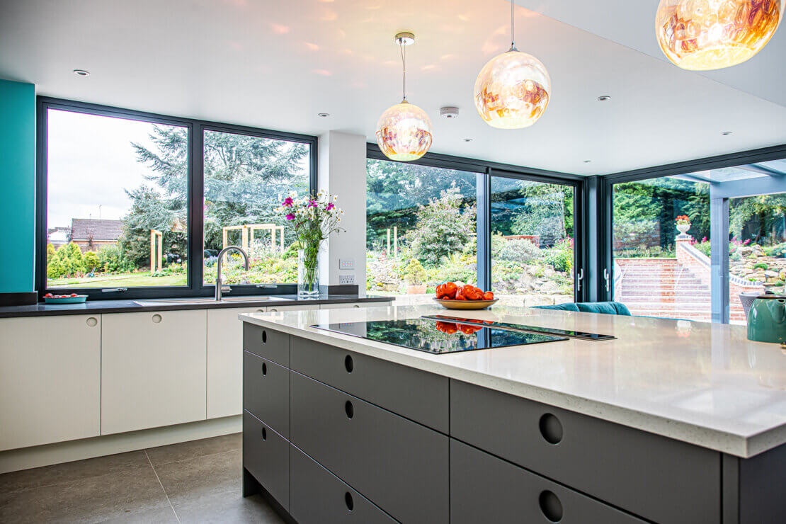 Grey kitchen with bespoke cut out handles and pendant lights in bright minimalism style