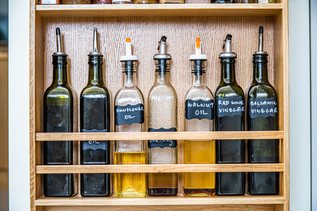 glass oil bottles displayed in oak spice rack
