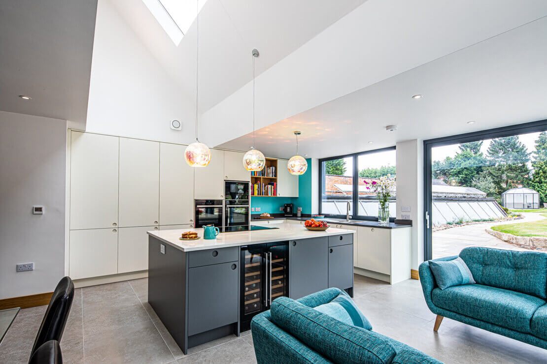 grey and white kitchen with high ceiling skylight and blue sofas