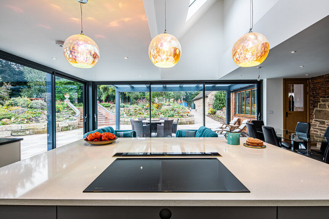 induction hob in quartz kitchen island with three pendant lights overhead