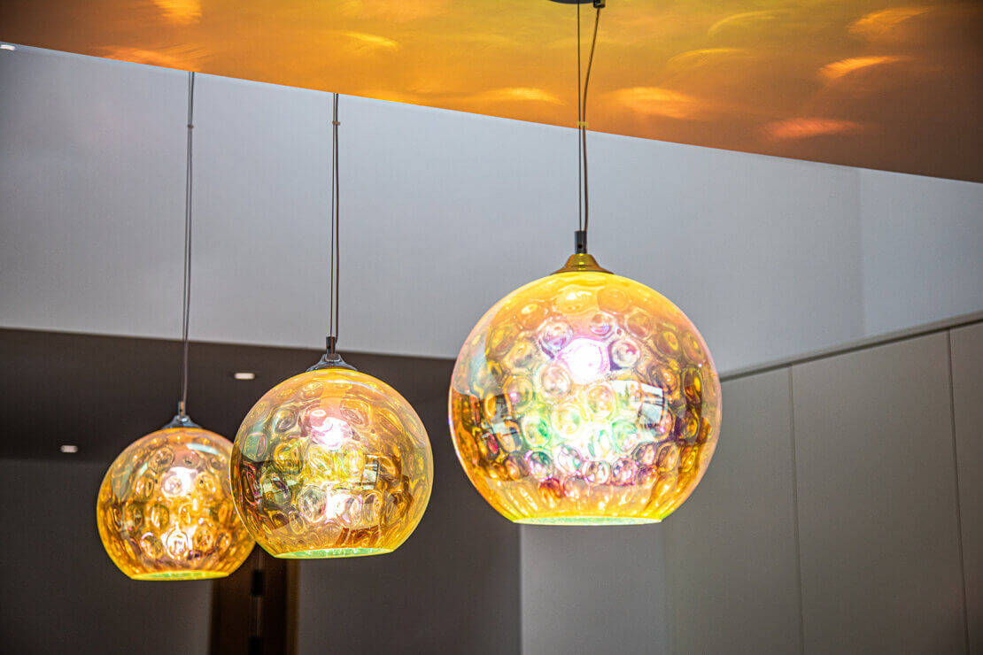 three iridescent pendant kitchen lights