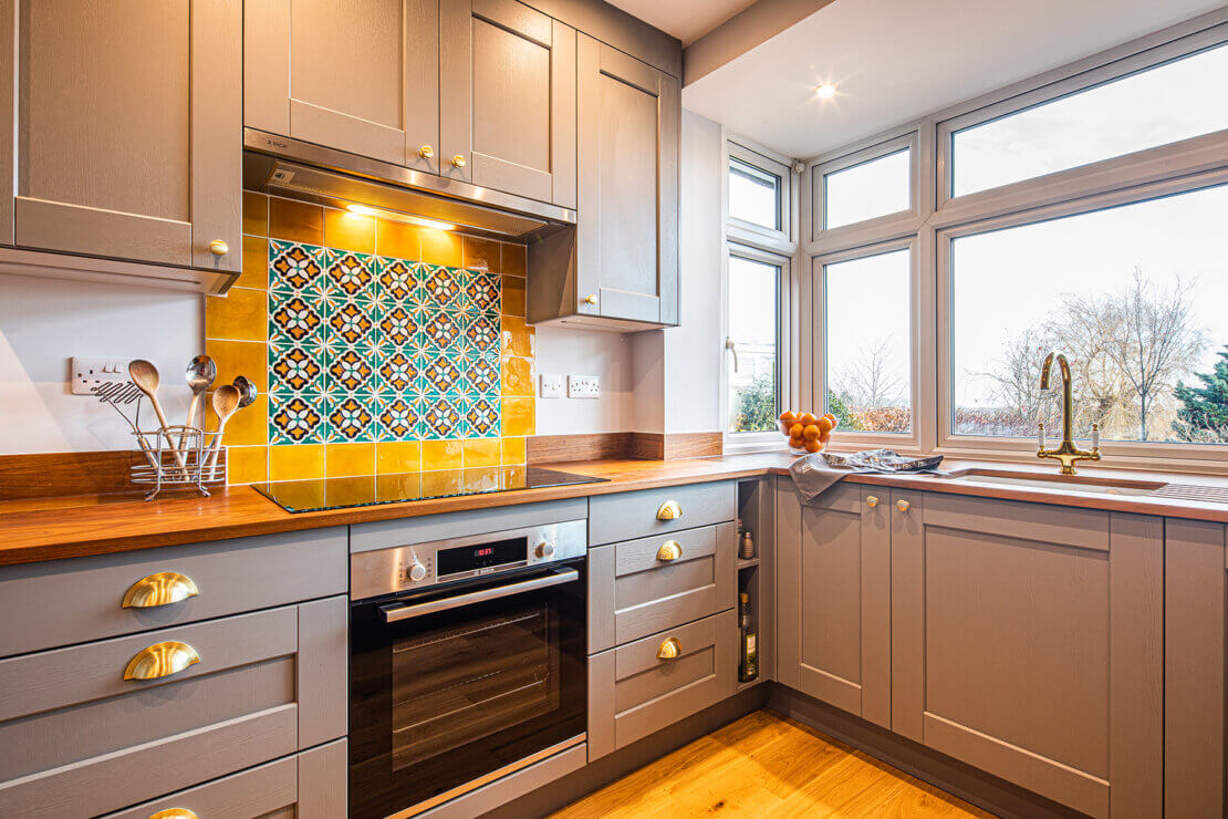 colourful tiled splashback in reclaimed timber kitchen