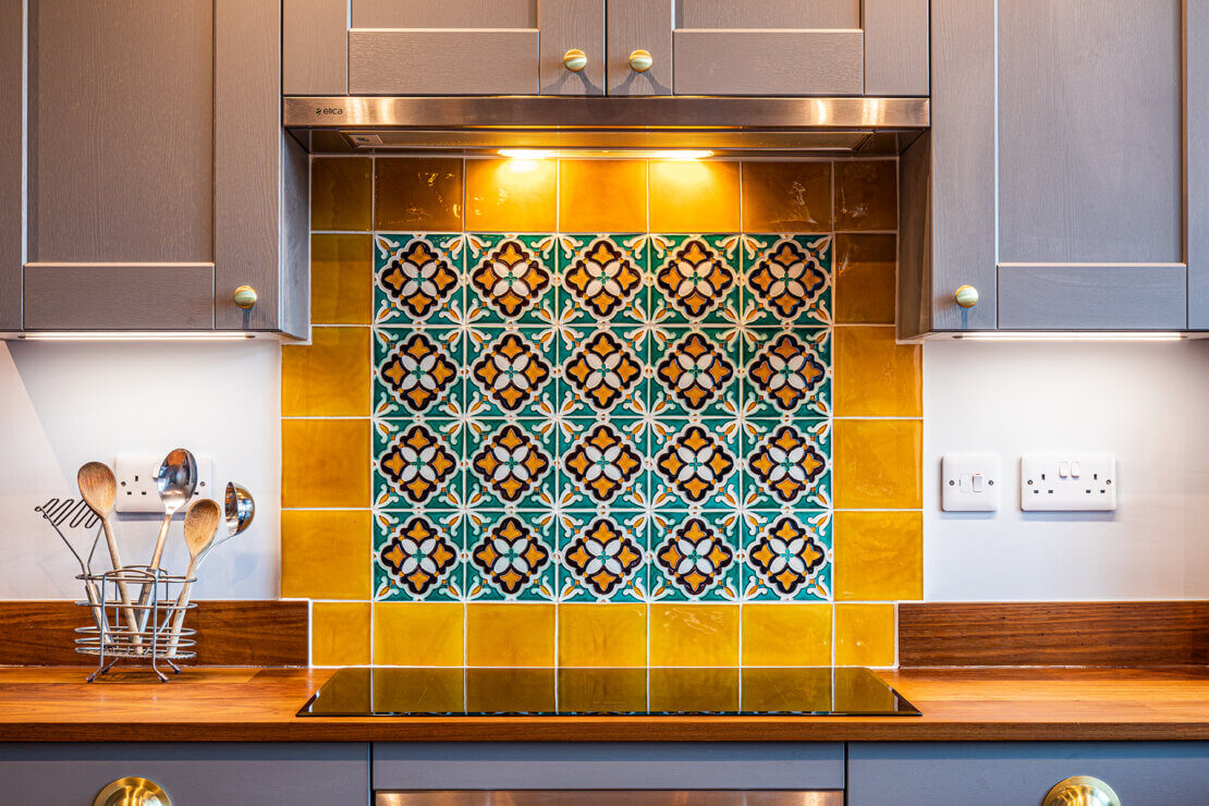 elica telescopic extractor fan above colourful tiled splashback