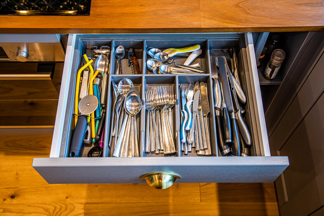 grey cutlery drawer with brass cup handle in reclaimed timber worktop