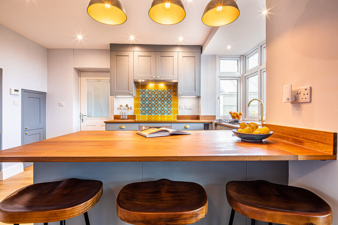 kitchen breakfast bar in u-shaped grey kitchen with brass handles
