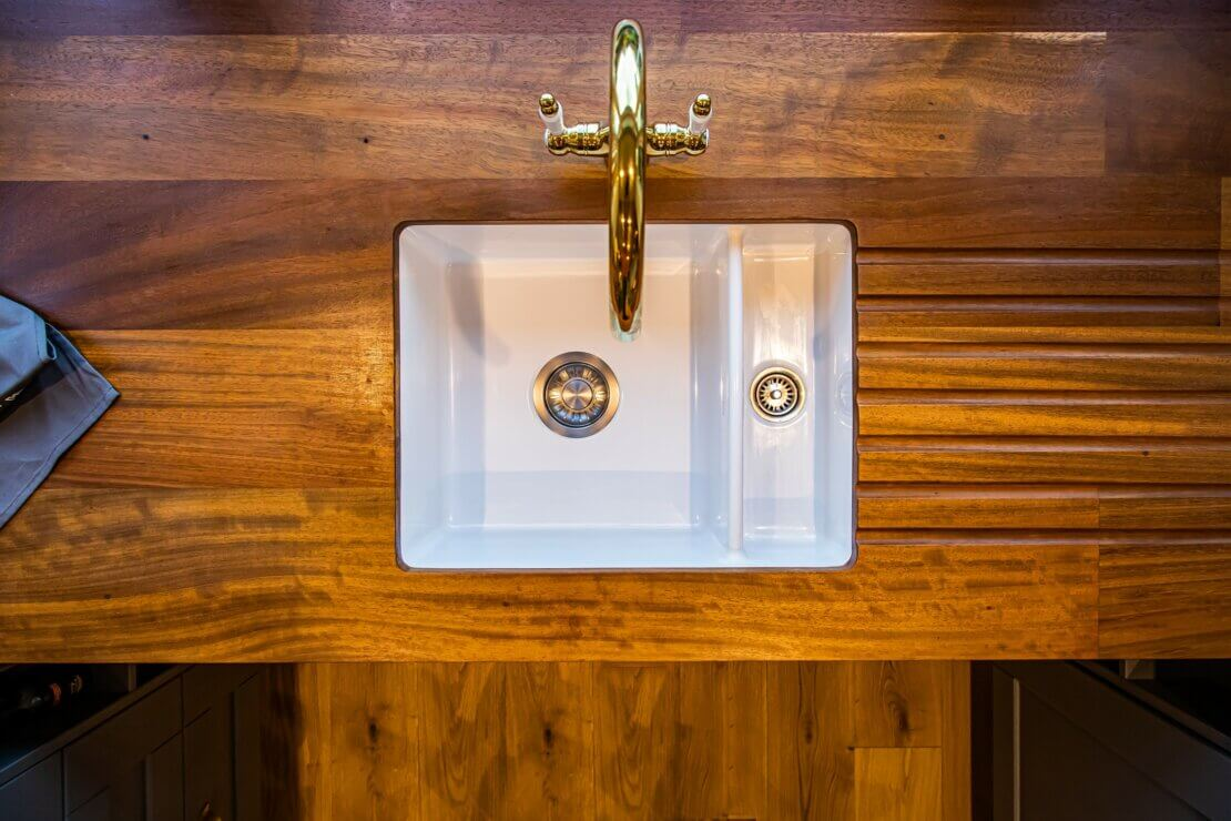 reclaimed timber kitchen worktop with ceramic sink and brass mixer tap