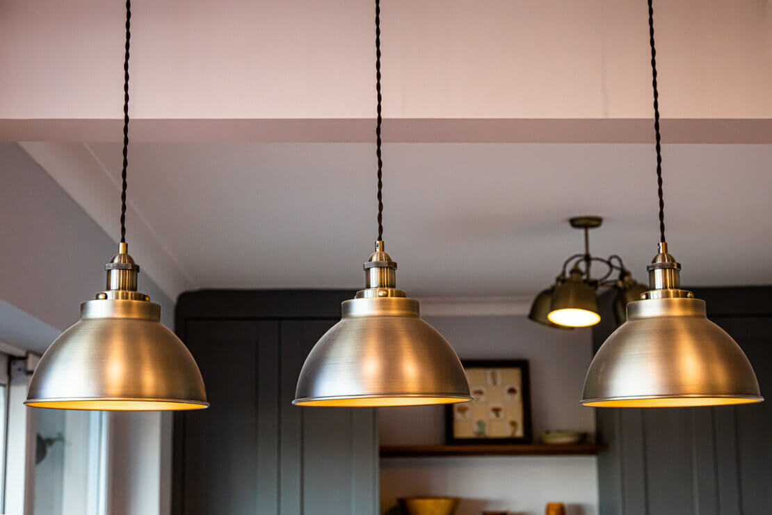 three metal pendant lights hanging over kitchen peninsula